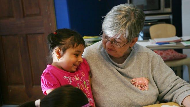 Sister Jean Fredricks, a preschool program director, works with students at Caroline House in Bridgeport, Conn., on Dec. 5.