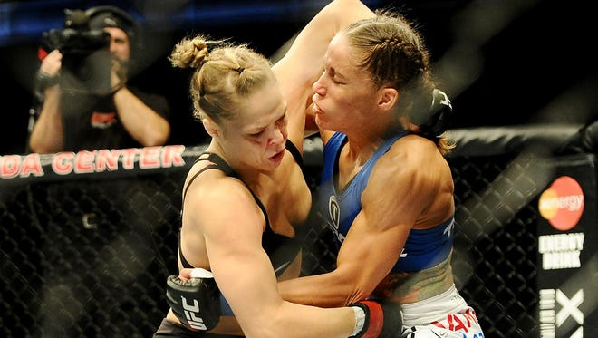 Ronda Rousey, left,  and Liz Carmouche fight during their UFC women's world bantamweight championship bout at the Honda Center Saturday.