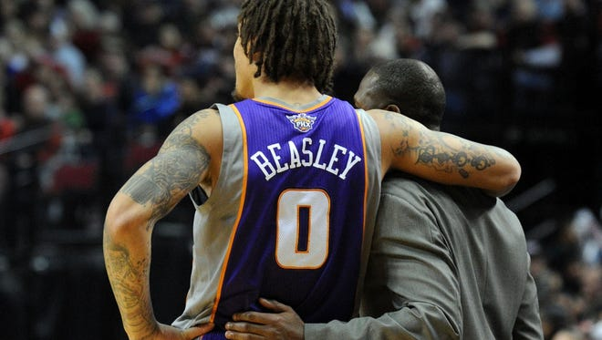 Phoenix Suns small forward Michael Beasley (0) puts his arm around Phoenix Suns head coach Lindsey Hunter during a timeout in the game against Boston on Saturday.