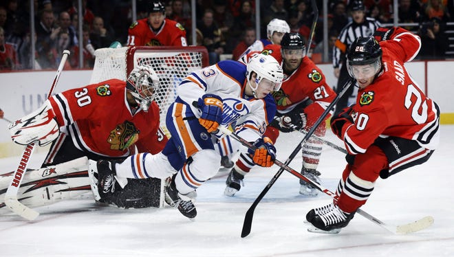Blackhawks left wing Brandon Saad (20) clears the puck after Oilers right wing Ales Hemsky was unable to get a shot off a rebound. Chicago won 3-2 in overtime.