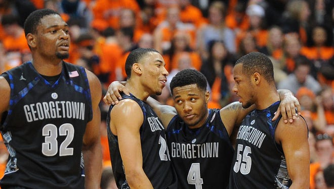 Georgetown center Moses Ayegba (32), forward Otto Porter Jr. (22), D'Vauntes Smith-Rivera (4) and Jabril Trawick (55) celebrate the Hoyas' 57-46 win at Syracuse.