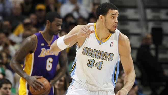 Denver Nuggets center JaVale McGee, front, celebrates scoring on a dunk as Los Angeles Lakers forward Earl Clark reacts in the background in the first quarter of an NBA basketball game in Denver on Monday, Feb. 25, 2013.