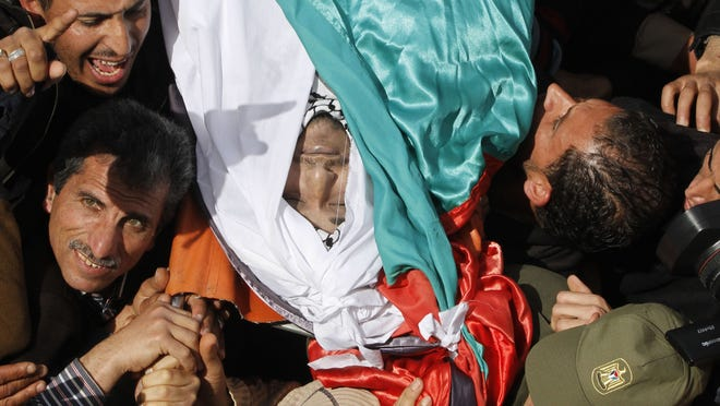 Palestinians carry the body of Arafat Jaradat during his funeral in the West Bank town of Saeer, near Hebron, on Monday.