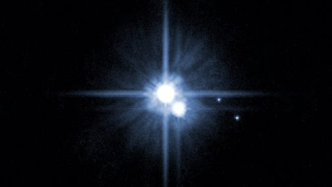 This 2005 image from the Hubble Space Telescope shows Pluto and three of it's five moons -- Charon, the largest, and Nix and Hydra. Two tiny moons discovered in the past two years will be named Vulcan and Cerebus, according to results of an online poll.