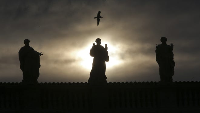 A seagull flies over statues at St. Peter's Basilica at the Vatican on Monday. Pope Benedict XVI has changed the rules of the conclave that will elect his successor, allowing cardinals to move up the start date if all of them arrive in Rome before the usual 15-day transition between pontificates.