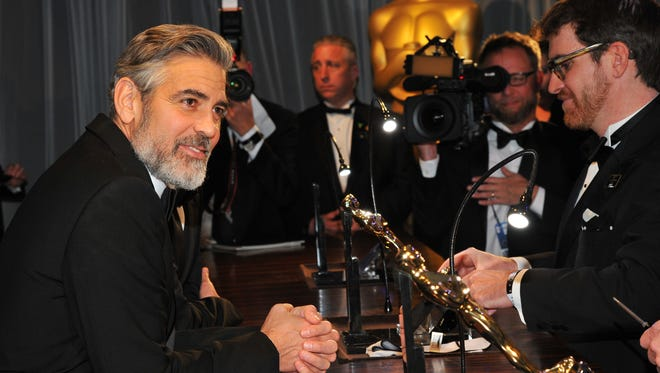 Producer George Clooney waits as his Oscar statuette is engraved after winning the award for best picture for 'Argo' at the Governors Ball.