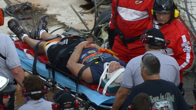 Emergency officials transport a spectator injured after a car hit a safety fence at Daytona International Speedway on Saturday.