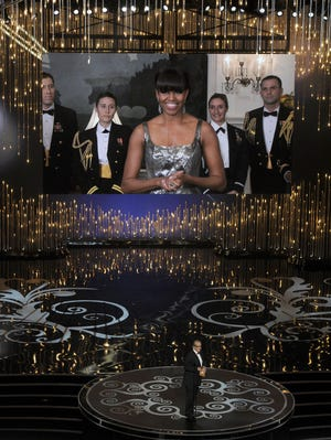 First lady Michelle Obama, appearing on screen, and Jack Nicholson present  best-picture award at Oscars.