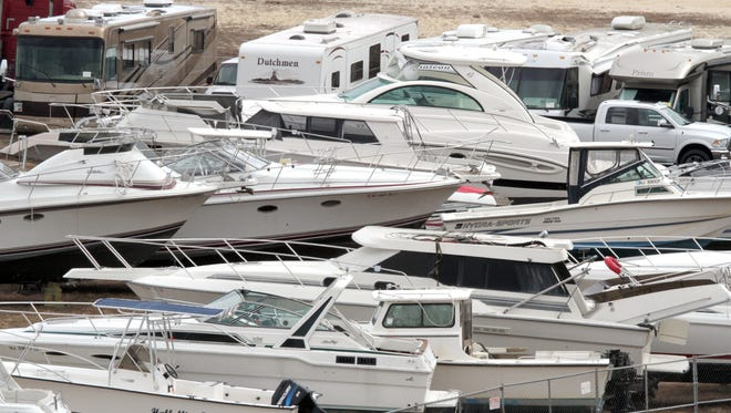 Hundreds of boats, motorcycles, recreation vehicles totaled during superstorm Sandy are now being stored in a lot at the end of a runway at Monmouth Executive Airport in Wall, N.J., while they are auctioned off.