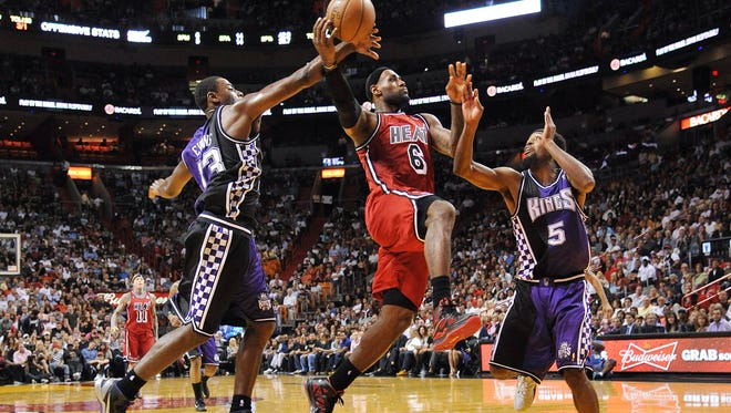 Miami Heat small forward LeBron James (6) drives to the basket as Sacramento Kings point guard Tyreke Evans (13) and small forward John Salmons (5) defend during the second half at the American Airlines Arena. The Heat won in a double overtime 141-129.