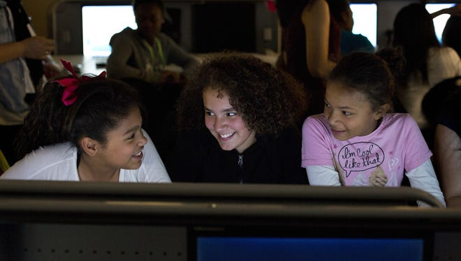 Sixth graders (left to right) Carrine Jenkins, 11, Gabriella Martinez, 11, and Asia Henphill, 11, participate in a computer programming class at South Shore K-8 School in Seattle.
