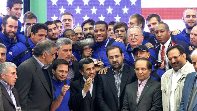 In this photo taken on Feb. 22, 2013 and released by China's Xinhua News Agency, Iranian President Mahmoud Ahmadinejad, fourth left in front row, stands with members of the U.S. freestyle wrestling team at the awards ceremony of the World Cup held in Tehran.