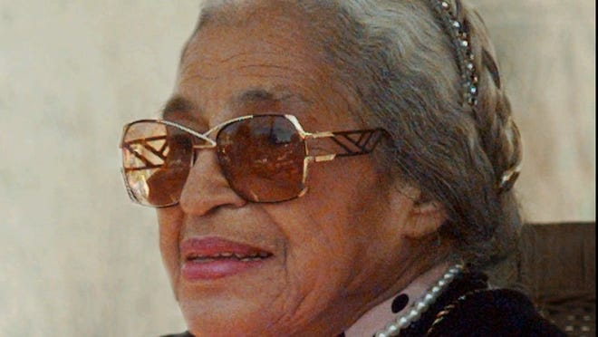 Rosa Parks, then 84, holds a program from the Rosa Parks Elementary School dedication during a 1997 ceremony in San Francisco.