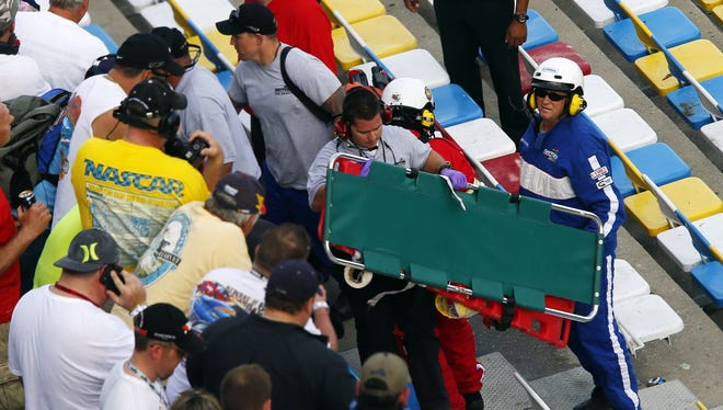 Track personnel carry a stretcher into the stands following a crash on the last lap of the DRIVE4COPD 300 at Daytona International Speedway.