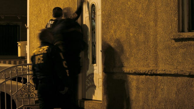 Immigration and Customs Enforcement officers knock on the door during a pre-dawn raid in Santa Ana, Calif.
