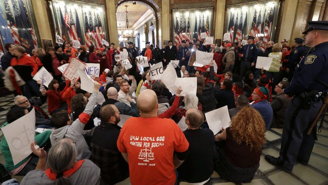 Protesters sit in the rotunda of the State Capitol in Lansing, Mich., on Dec. 11, 2012 demonstrating against right-to-work legislation passed by the house.