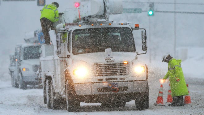 Westar Energy crews work on snow-covered power lines in Lawrence, Kan., on Feb. 26.