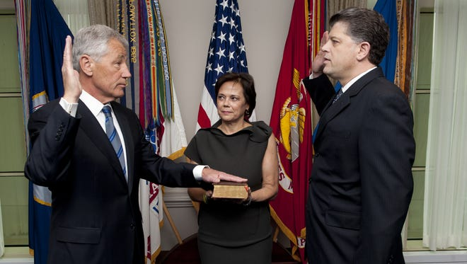 Chuck Hagel, with his wife, Lilibet, holding a Bible, is sworn into office by Defense Department official Michael  Rhodes on Wednesday.