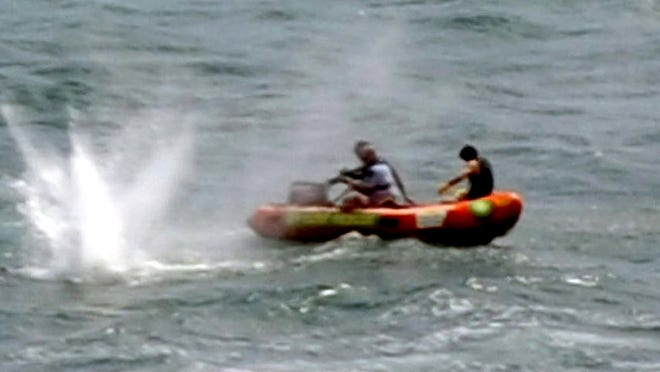 Police in rubber boats shoot at a shark off Muriwai Beach near Auckland, New Zealand, as they attempt to retrieve a body following a fatal shark attack.