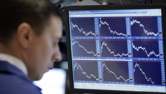 A specialist watches stocks fall on his monitor from his booth on the floor of the New York Stock Exchange.