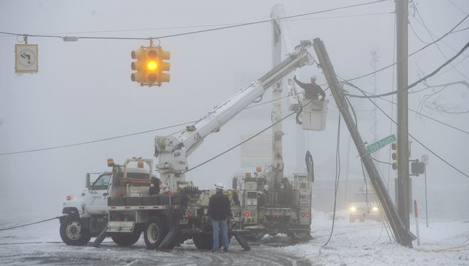Fog shrouds work crews repairing downed power lines on Wednesday in Southfield, Mich. The storm dropped at least 7 inches of snow on parts of Michigan.