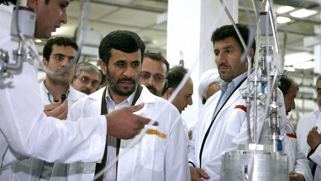 Iranian President Mahmoud Ahmadinejad, , listens to a technician during his visit of the  Natanz Uranium Enrichment Facility.