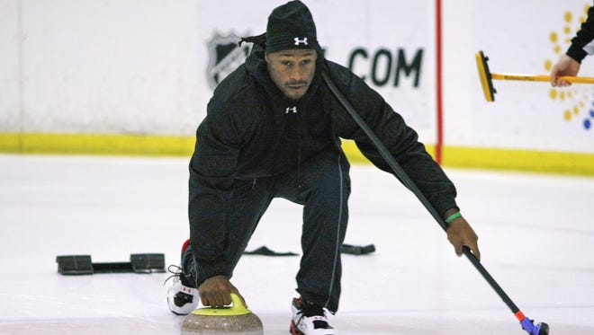 In this photo taken Nov. 3, 2009, San Francisco 49ers tight end Vernon Davis learns the game of curling  with members of the San Francisco Bay Area Curling Club,  in San Jose.