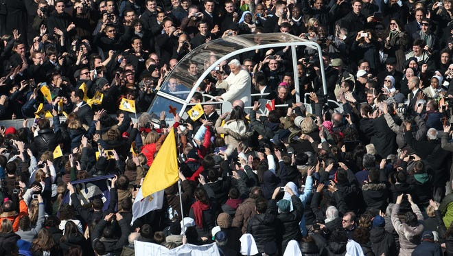 Pope Benedict XVI waves to he faithful as he arrives in St Peter's Square on Wednesday in the Vatican for his last weekly public audience.