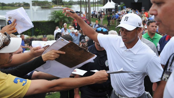 Tiger Woods signs autographs after the pro am of the Honda Classic at PGA National on Wednesday.