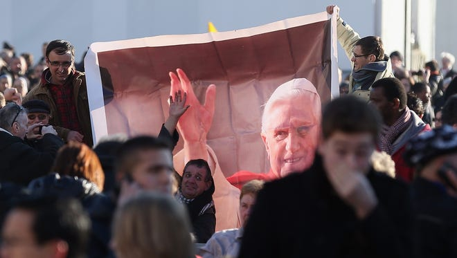 Pilgrims hold a banner as they attend Pope Benedict XVI's final general audience on Wednesday.