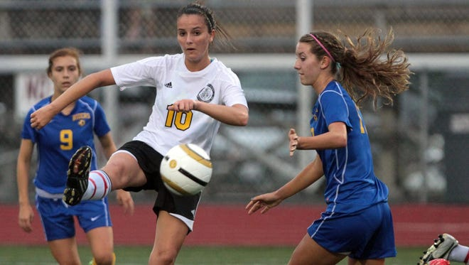 Hailey Lawler, center, of Padua Academy High School in Wilmington, Del., plays the ball past Grace Wilt of Caesar Rodney High School in Camden, Del.