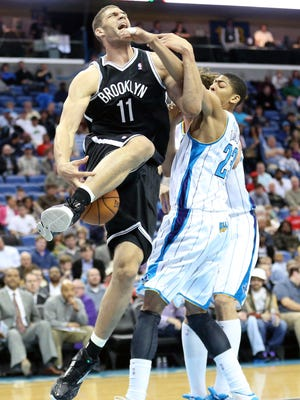 Nets center Brook Lopez, left, and Hornets forward Anthony Davis get tangled during Tuesday's Brooklyn win.