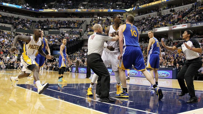 Referees try to separate Pacers center Roy Hibbert and Warriors forward David Lee during a fight Tuesday.