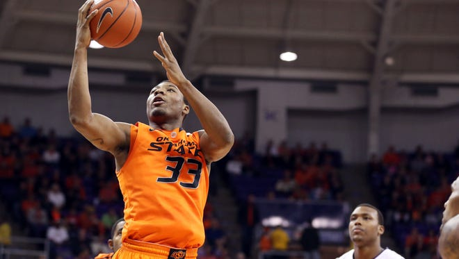 Oklahoma State Cowboys guard Marcus Smart shoots against TCU Horned Frogs forward Devonta Abron during the first half at the Daniel-Meyer Coliseum.