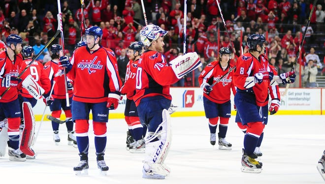 Washington Capitals goalie Braden Holtby and teammates wave to the crowd after beating the Carolina Hurricanes 3-0 at Verizon Center.