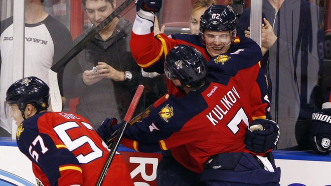 Florida Panthers center Tomas Kopecky is congratulated by  defenseman Dmitry Kulikov after his third goal of the game against the Pittsburgh Penguins in the third period at the BB&T Center.