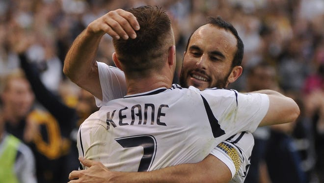In a file photo from Dec. 1, 2012, Los Angeles Galaxy midfielder Landon Donovan (10) hugs teammate Robbie Keane (7) after Keane's goal against Houston in the MLS Cup at Home Depot Center.
