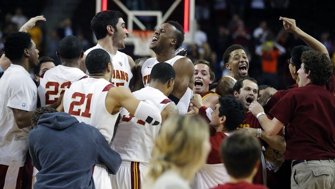 Southern California basketball players celebrate on the court after defeating Arizona in Los Angeles.