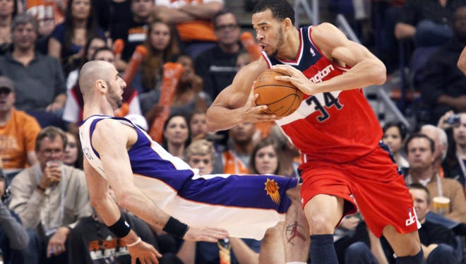 Phoenix Suns center Marcin Gortat, left, of Poland, falls backward to the floor as Washington Wizards center JaVale McGee, right, is called for a charge last season. The league set out to stop these kinds of plays this season.