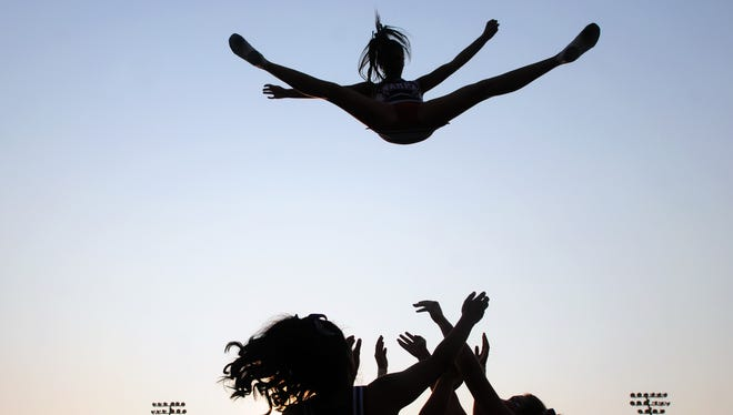 A cheerleader from Nampa High School is thrown into the air as the cheer squad practices their stunts before a game in Nampa, Idaho.