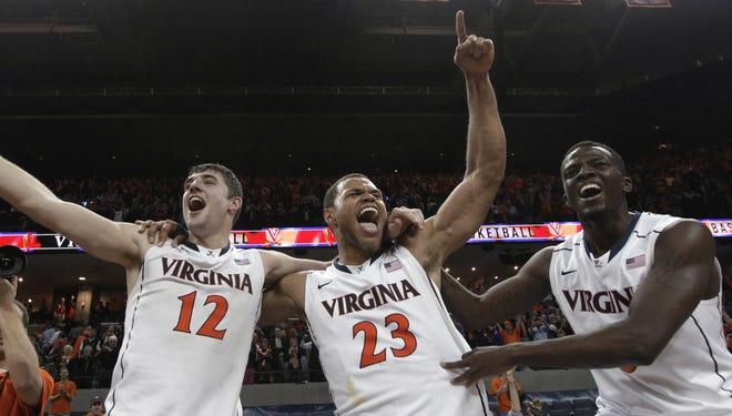 Virginia's Joe Harris (12), Justin Anderson (23) and Teven Jones (5) celebrate Virginia's 73-68 win over Duke in Charlottesville, Va., Thursday, Feb. 28, 2013. Harris had 36 points.