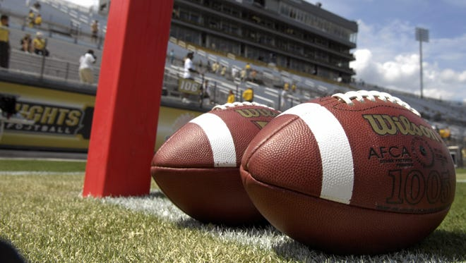 Two footballs rest in the end zone before a college football game.