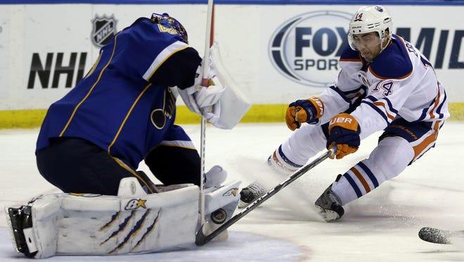 Edmonton Oilers' Jordan Eberle reaches to poke the puck past St. Louis Blues goalie Jaroslav Halak. The Blues scored four straight goals to beat Edmonton 4-2.