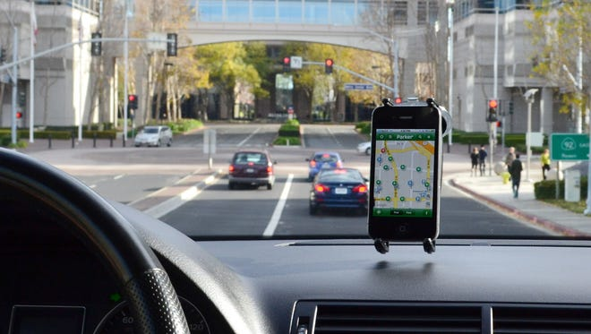 The Parker mobile app from Streetline is displayed on a smartphone device in an automobile.