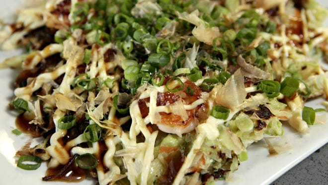 """""""'Okonomiyaki' means 'cook as you like,' and these thick, savory pancakes might come packed with your choice of shredded cabbage, sliced green onion, corn, thin strips of pork belly, noodles, mushrooms, a fried egg or pretty much anything else you fancy."""""""