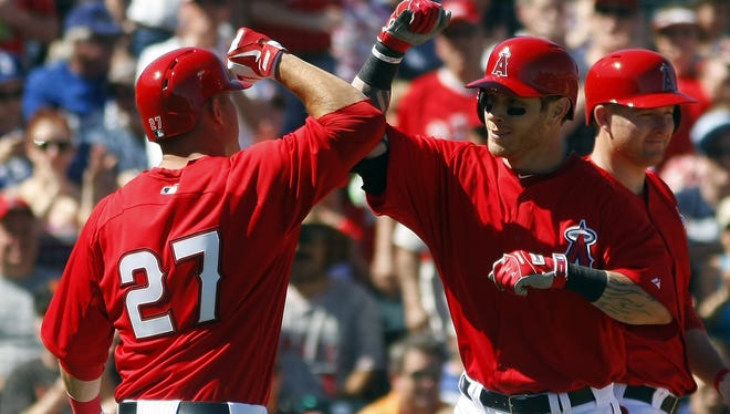 Los Angeles Angels left fielder Josh Hamilton, right, celebrates with Mike Trout after hitting a two run home run against the Los Angeles Dodgers in the first inning at Tempe Diablo Stadium.