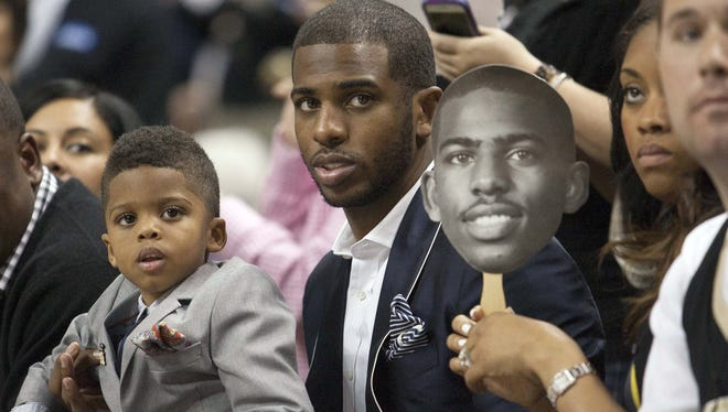 Los Angeles Clippers player Chris Paul holds his son, Christopher Paul, while his wife Jada Paul holds a sign during the second half of the game between the Wake Forest Demon Deacons and the Maryland Terrapins at Lawrence Joel Veterans Memorial Coliseum.
