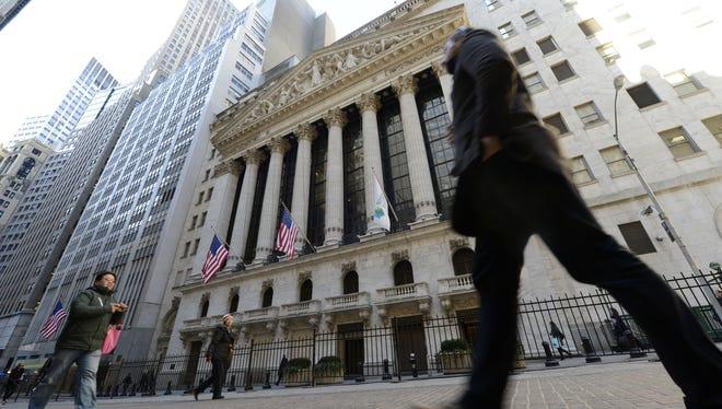 Pedestrians walk in front of the New York Stock Exchange.