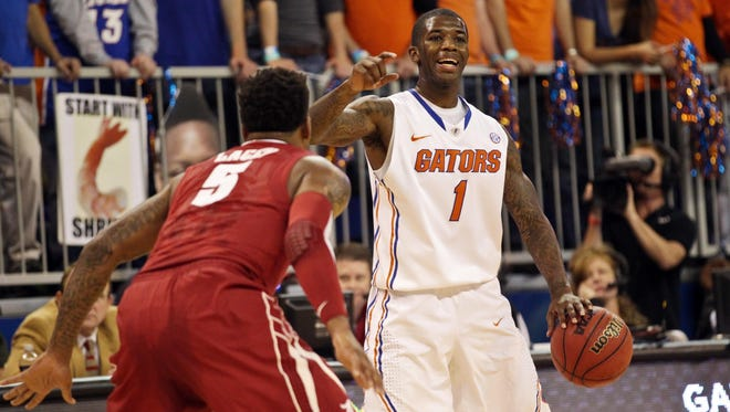 Florida Gators guard Kenny Boynton is defended by Alabama Crimson Tide guard Trevor Lacey during the first half at the Stephen C. O'Connell Center.