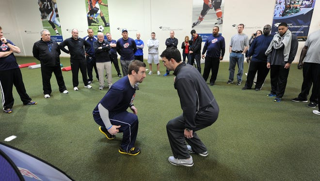 Instructor Andy Ryland, left, and Gabe Infante, coach at head coach at St. Joe's Prep in Philadelphia, demonstrate the proper tackling technique that teaches not to wrap up, as has been the case for many years.